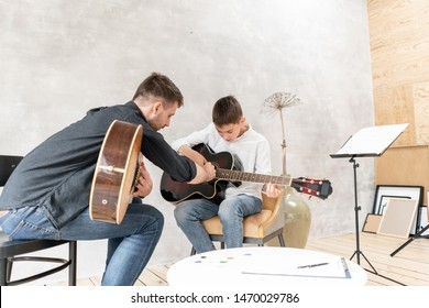 Two brother playing guitar. Older brother teaches younger one to play chords correctly