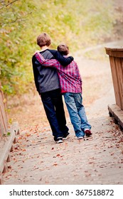 Two brothers with arms around each other walking on a bridge outdoors.