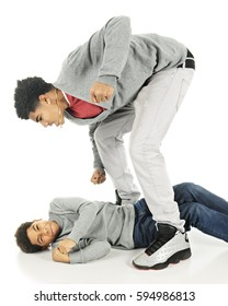 Two brothers fighting.  A tall older teen stands over his elementary brother who is cringing while nearly flat on his back.  On a white background.