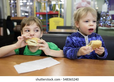 Two brothers have sandwiches at table in cafe