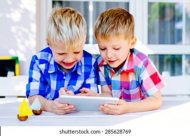 Two brothers having fun playing on digital tablet outside the home