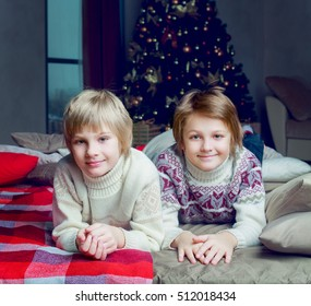 two brothers at home with the Christmas tree and presents