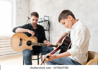 Two brothers learn to play acoustic guitar. The older brother tunes the guitar while the younger one runs his finger along the strings