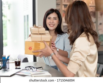 Two brothers owener of small family business. Woman holding Cardboard Box preparing it for delivery. online seller business work from home.