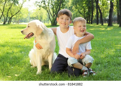 Two brothers in the park with a golden retriever dog