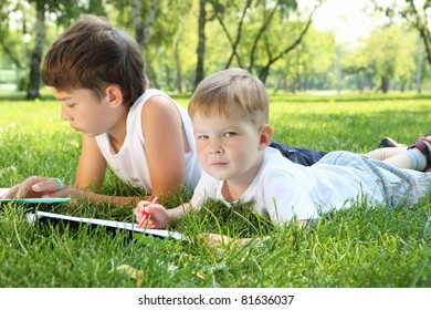 Two brothers in the park reading a book together