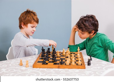 Two brothers are playing chess at home.