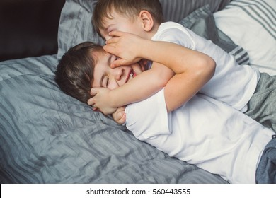 Two brothers are playing on the bed. Christmas.