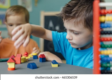 Two brothers playing with wooden blocks making houses and learning shapes at home