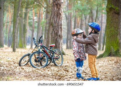 Two brothers preparing for bicycle riding in spring or autumn forest park. Older kid helping sibling to wear helmet. Safety and protection concept. Happy boys best friends having good time together