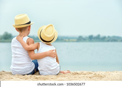 Two brothers relaxing on the beach of the lake.The little boy tenderly embraces his older brother.