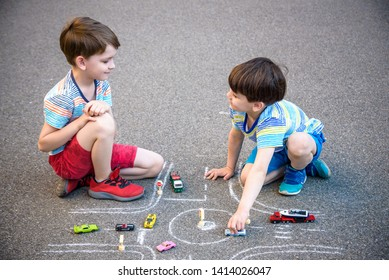Two brothers sibling kid boy having fun with picture drawing traffic car with chalks. Creative leisure for children outdoors in summer. Difficult traffic rules education friendship concept.