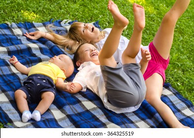 Two brothers and sister having fun on the meadow on sunny summer day.