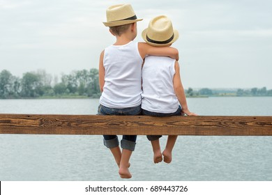 Two brothers in a straw hats sitting on the pier and looking at the lake.Summer vacation .