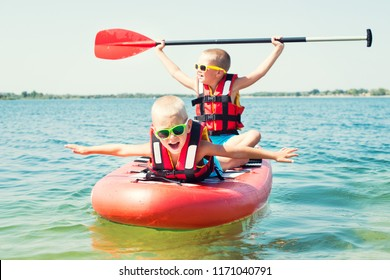 Two brothers swimming on stand up paddle board.Water sports , active lifestyle.