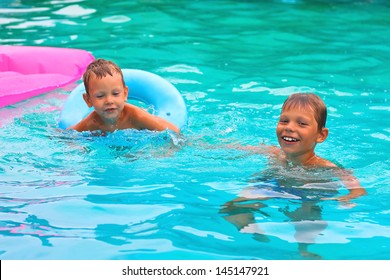 Two brothers are swimming in the pool