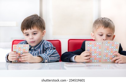 two brothers at the table playing a board game