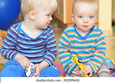 Two brothers wearing colored shirt are playing with cars.  One is watching the other. Child concept, family concept.