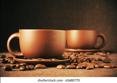 Two brown ceramic cups of coffee and roasted coffee beans on brown canvas.