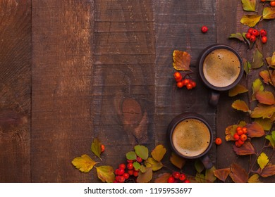 Two brown clay cups of black coffee and branches of autumn leaves (Spiraea Vanhouttei) with small red rowan's fruits on the old wooden table. Top view.