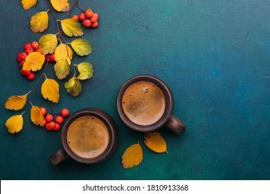 Zwei braune Tassen schwarzen Kaffees, Äste mit kleinen Herbstblättern und rote Rowan-Früchte auf dunkelblaugrünem, lackiertem Holzhintergrund mit Leerzeichen für Text .  Flat lay. Selektiver Fokus.