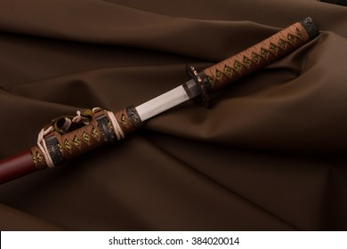 two brown cream Japanese sword on a leather brown background