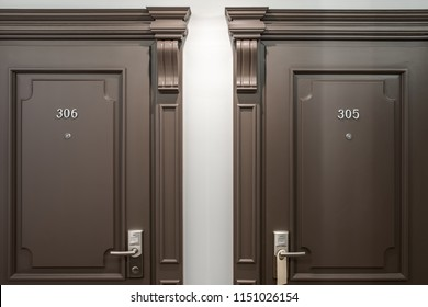 Two brown doors with room numbers on them on the light wall background in the hotel. Closeup horizontal photo.