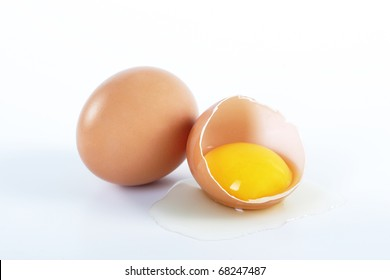 Two brown eggs on a white background. One egg is broken.