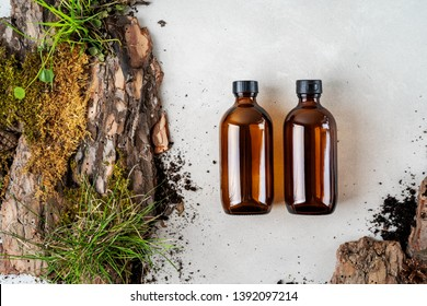 Two brown glass Mock up bottles of shampoo and conditioner of body care cosmetics over Natural background of real tree bark, tiny mosses and grass organic for cosmetic products with copy space.