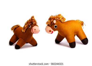 Two brown knitted hobby horses isolated on white background.