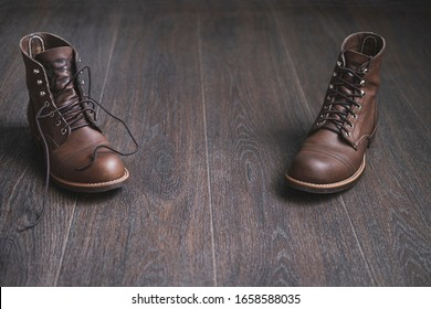 Two brown  leather men boots, one with sleazy untied  laces and one with tied shoelaces  opposite each other on a wooden floor. Vintage men footwear.