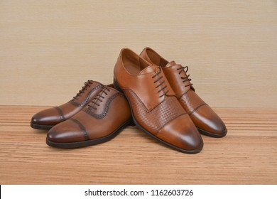 Two brown leather shoes on a wooden background.