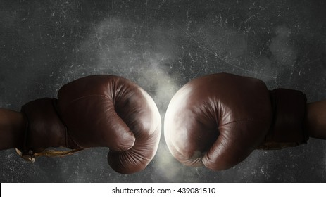 Two brown old boxing gloves hit together