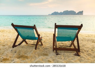 Two brown sunbeds on sunset on yellow sand tropical beach Thailand - Shutterstock ID 285131618