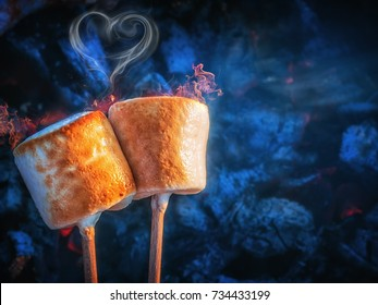 Two brown sweet marshmallows roasting over fire flames. Smoke in form of hearts. Marshmallow on skewers roasted on charcoals