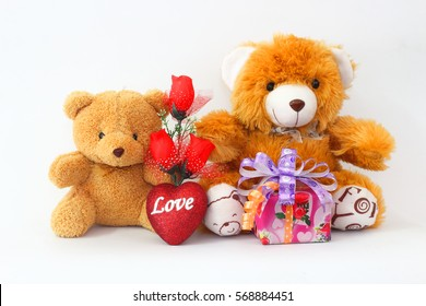 Two brown teddy bear with a red rose and a gift box on a white background.