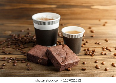 Two brownie cakes and paper mug of cappuccino and espresso on a wooden background