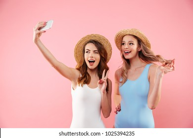 Two brunette and blonde women in one-piece swimsuits and straw hats smiling and taking selfie on smartphone isolated over pink background