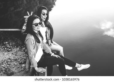 Two brunette women relaxing outdoor near lake