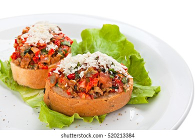 Two Bruschetta with vegetables and grated Parmesan cheese on a plate.