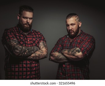 Two brutal mans with beards and tattoo isolated on grey background. Crosed arms.