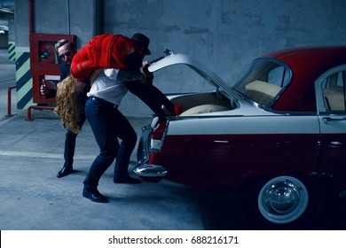 Two brutals kidnapping men kidnap a young long haired blonde woman, holding her on the shoulder and puts her inside in a car trunk of a vintage car at the dark underground parking. Horizontal view.