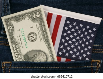 two buck and american flag lie inside at back pocket at blue jeans fabric background. two 2 dollar bill banknote
