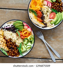 Two buddha bowl. Clean and balanced healthy food concept. Chicken grilled steak, rice, spicy chickpeas, black and white quinoa, avocado, carrot, zucchini, radish, tomatoes on wooden table top view