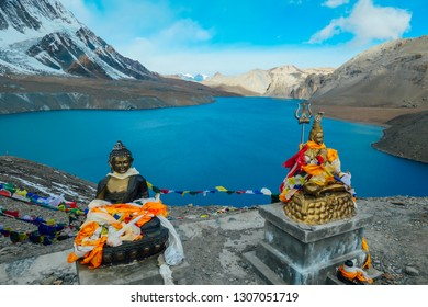 Two Buddha statues at the Tilicho Lake, covered with prayer's flags. Blue and calm surface of the lake, mountains covered in the shadow, sunlight in the back. Annapurna Circuit Trek, Nepal.