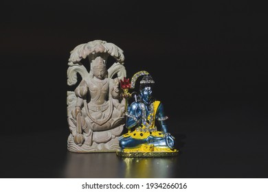 Two Buddhist figurines, Shiva and Buddha, on a black isolated background. Close-up, banner, copy space.