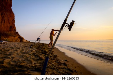 Two buddies are catching fish from the sandy beach with a few fishing rods, morning over Mediterranean sea.