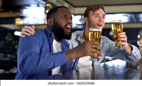 Two buddies drinking beer and watching sport competition in pub, leisure