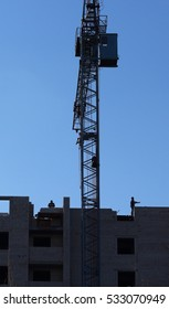 Two builders build a house. Near the tower crane. Construction a block of flats