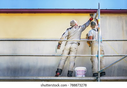 Two builders on safety scaffolding  make yellow decorative plaster on the new house wall. Construction